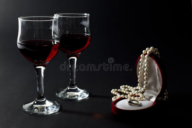 Collier de perle et anneau d'or dans la boîte à bijoux avec deux verres à vin remplis de vin rouge d'isolement sur le noir image stock