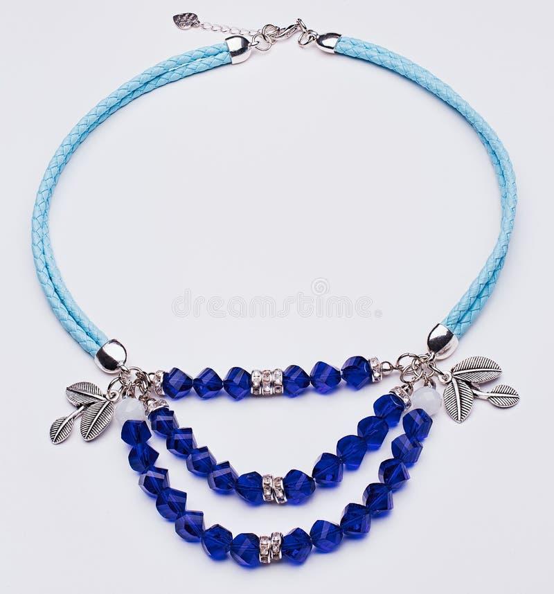 Collier en cuir bleu avec des feuilles d'argent et gemmes bleues images stock