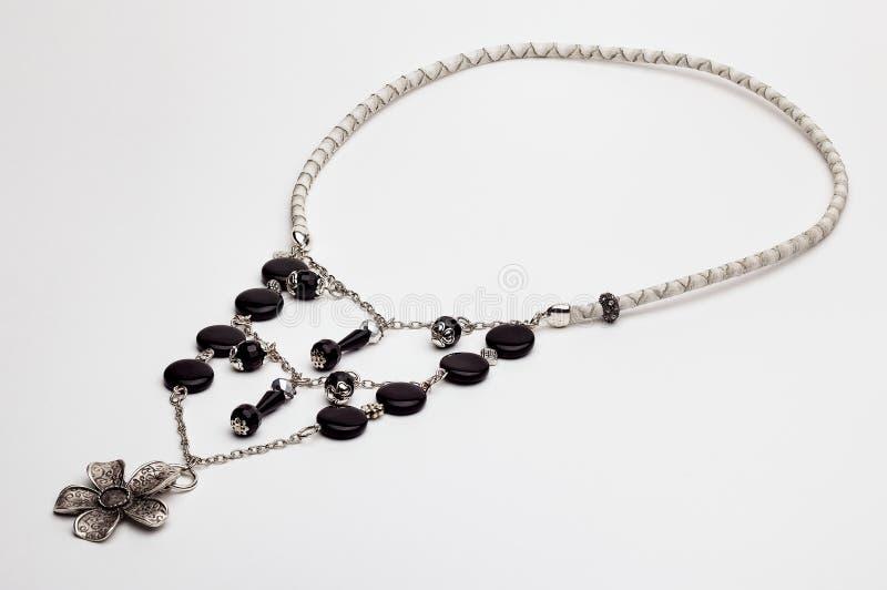 Collier en cuir noir et blanc avec une fleur argentée images stock