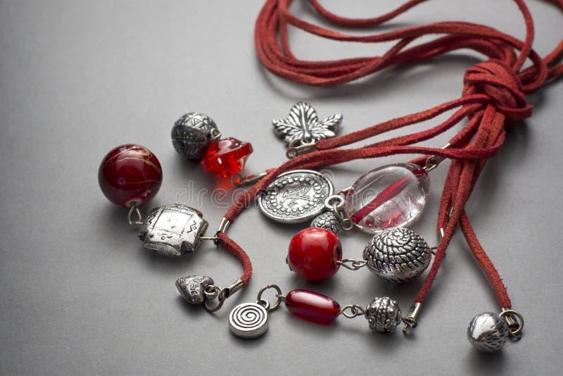 Collier ficelé par rouge avec des perles et des bibelots image stock