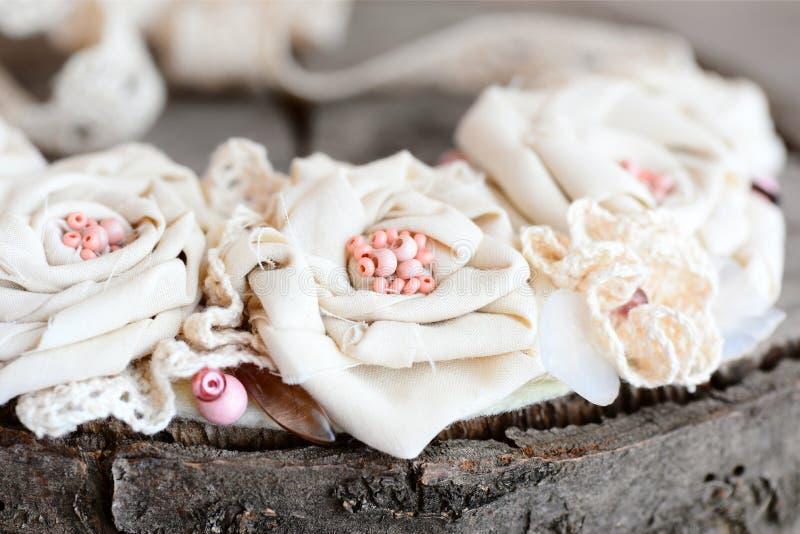Collier mou chic minable de tissu de coton, d'équilibres de dentelle, de perles et de base de feutre sur un fond en bois Collier  images stock
