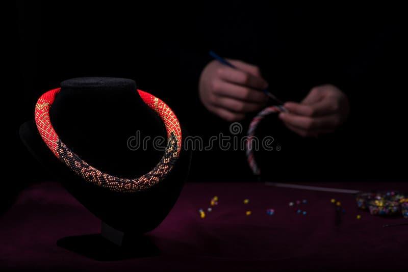 Collier multicolore des perles sur un mannequin Sur l'avion noir arrière la fille tricote les perles image stock