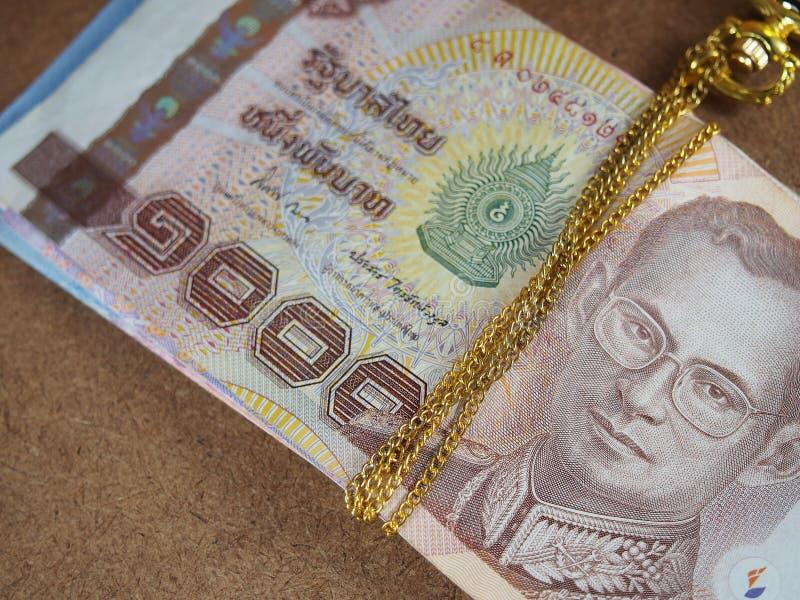 Collier obligatoire d'or avec l'argent thaïlandais de billets de banque photographie stock libre de droits