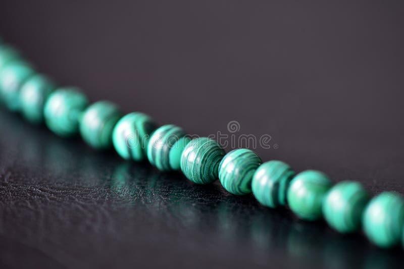 Collier vert de malachite sur un fond foncé photo stock