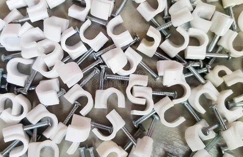 Colliers de câble en plastique avec les clous en acier images stock