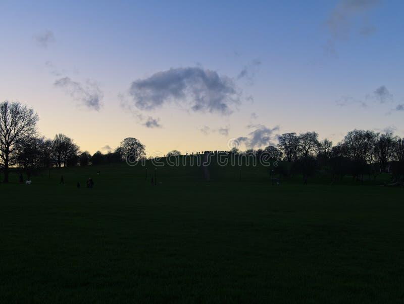 Collina della primaverina Bello cielo blu ed arancio al tramonto Siluetta della gente che gode della vista sopra la collina fotografie stock libere da diritti