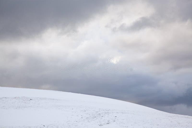 Collina e cielo blu di Snowy immagini stock