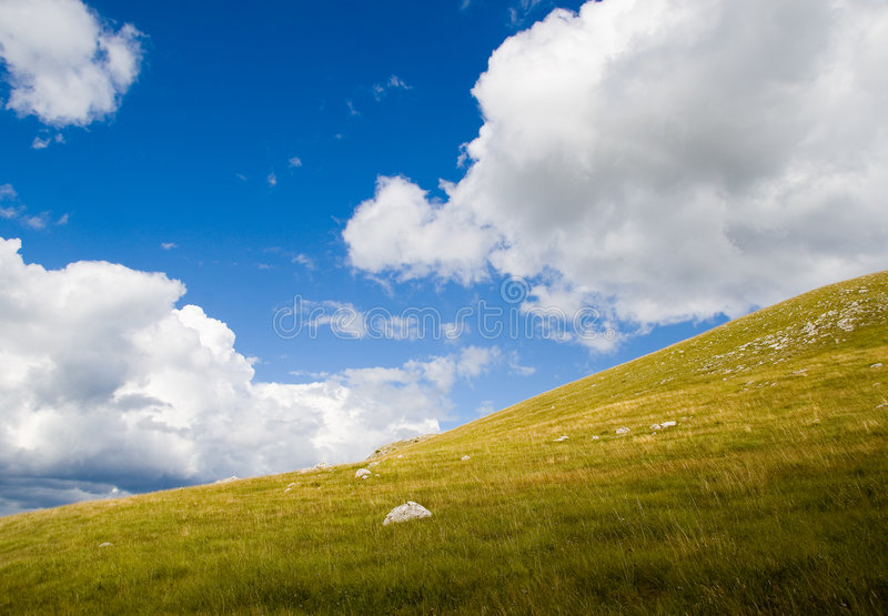 Collina verde con il cielo nuvoloso immagini stock