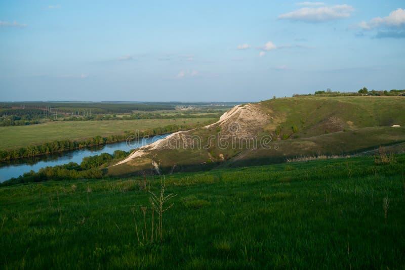 Collina verde vicino al fiume fotografie stock