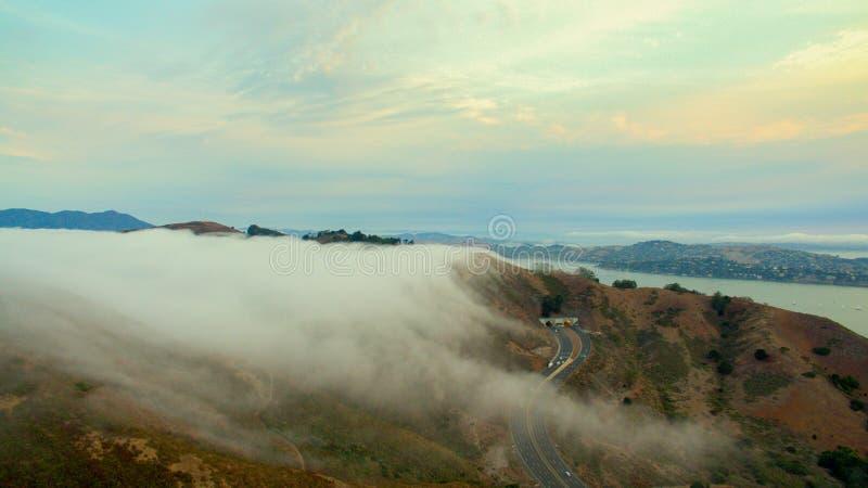 Colline che tengono indietro nebbia all'alba immagini stock