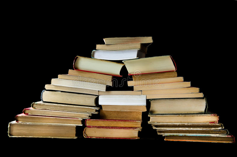 Colline de vieux livres sur le noir images stock