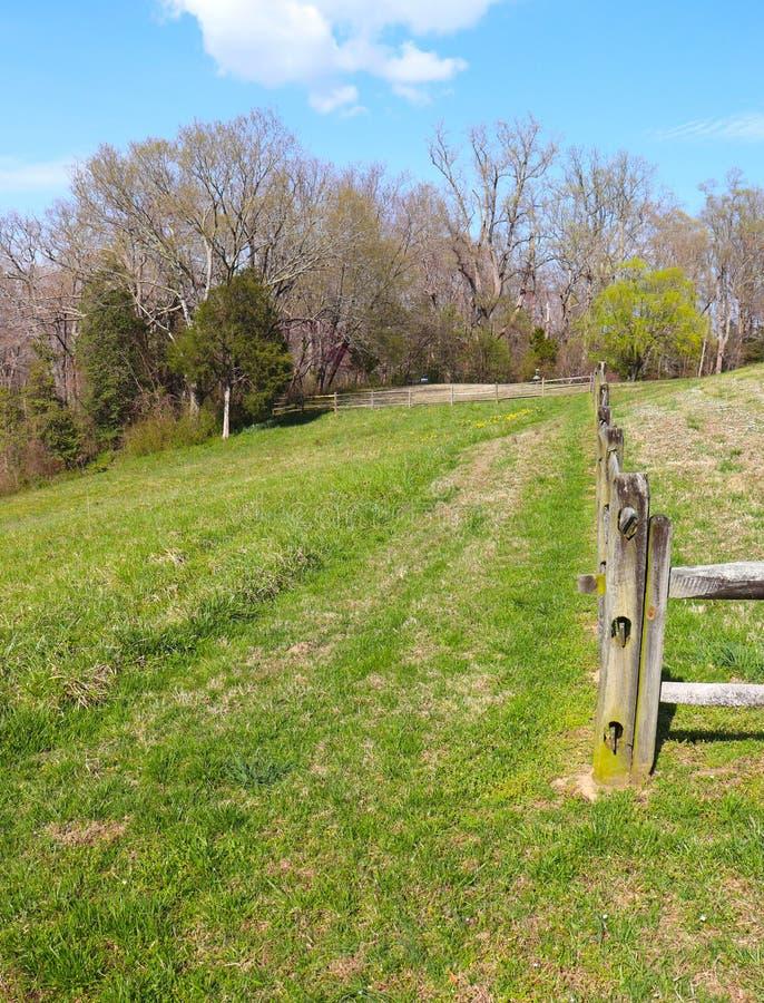 Colline herbeuse et barrière en bois taillée rugueuse photographie stock libre de droits