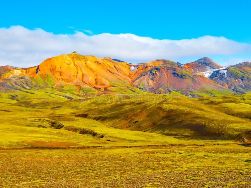 Colline verdi e terra rocciosa nera degli altopiani islandesi lungo la traccia di escursione di Laugavegur, Islanda Colpo soleggi fotografia stock libera da diritti