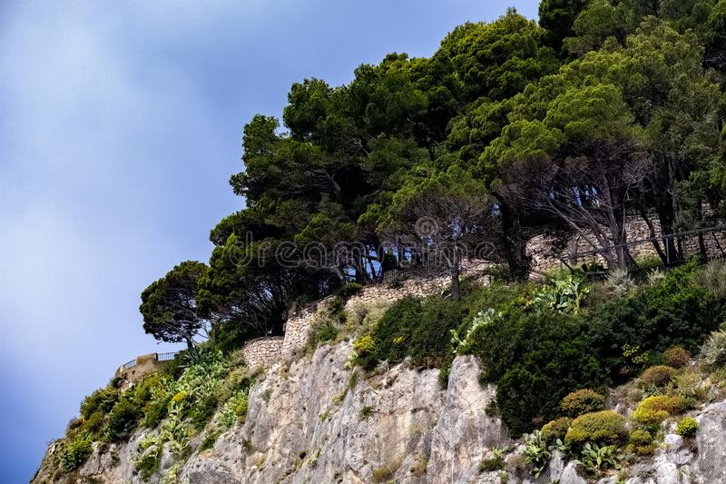 Colline verte, île tropicale, nuages et roches photos stock