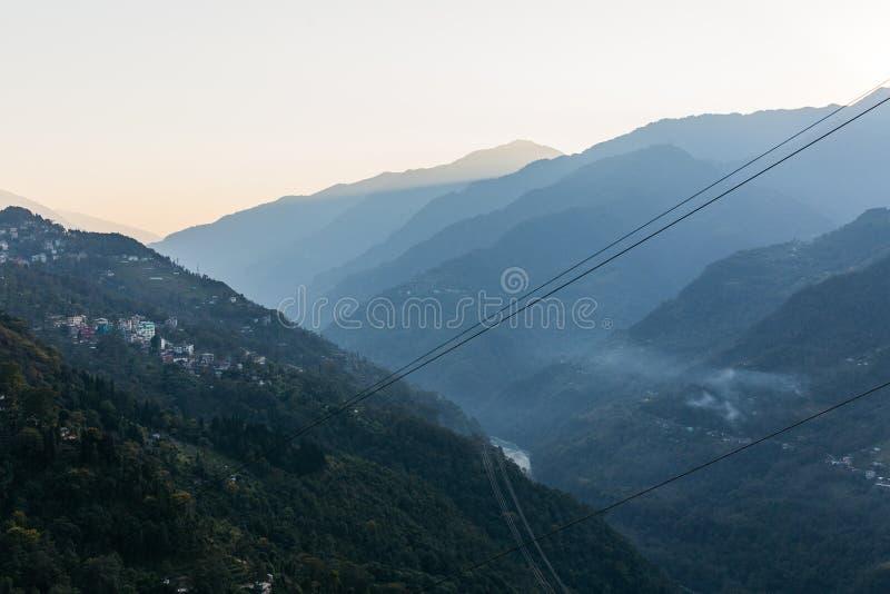 Colline verte près de montagne de Kangchenjunga avec des nuages ci-dessus, des arbres et le village avec la lumière du soleil qui image stock