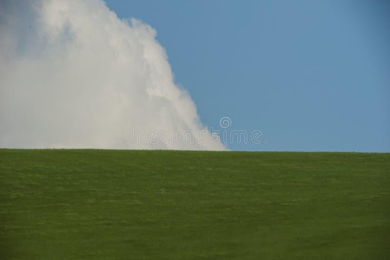 Collines de roulement de ressort et sur le ciel bleu et les nuages de fond image libre de droits
