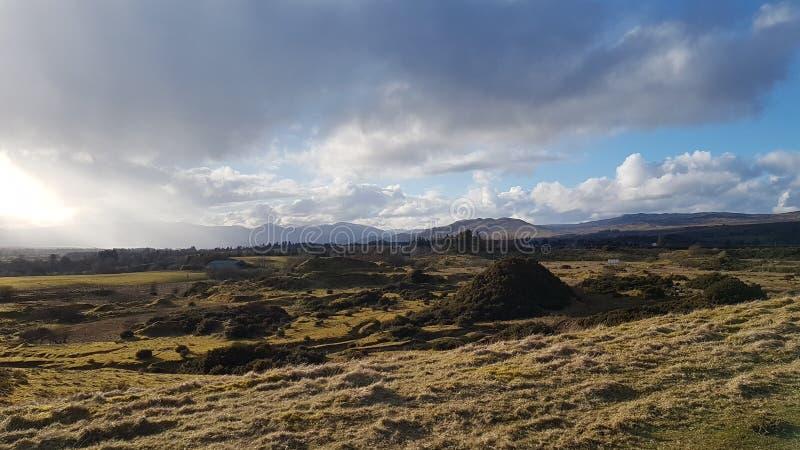 Collines et montagnes tôt de ressort avec les nuages et le soleil photo stock
