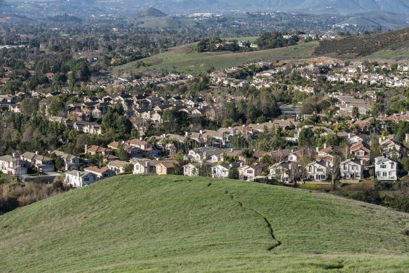 Collines, maisons, prés et traînées suburbains photo libre de droits