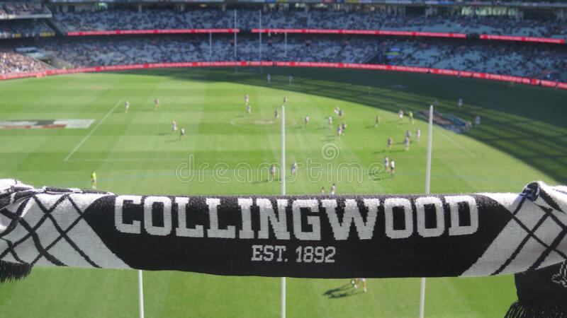 Collingwood Magpies supporter scarf with blurred background view of Melbourne Cricket Ground field during a footy game. Melbourne, Australia stock image