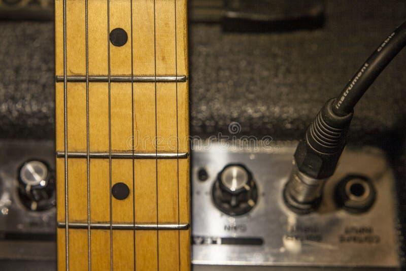Collo della chitarra sopra il dispositivo dell'amplificatore e l'audio cavo immagine stock