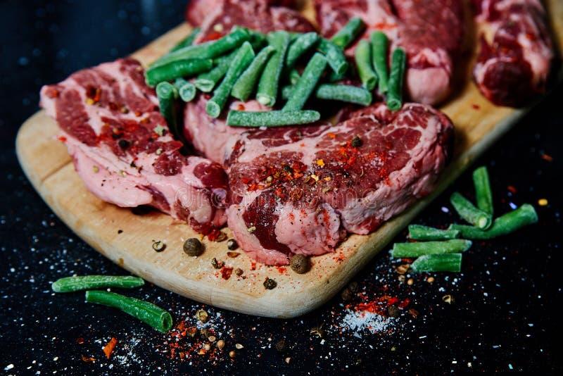 Collo fresco della carne di maiale della carne cruda sul bordo di legno sulla tavola nera immagini stock libere da diritti