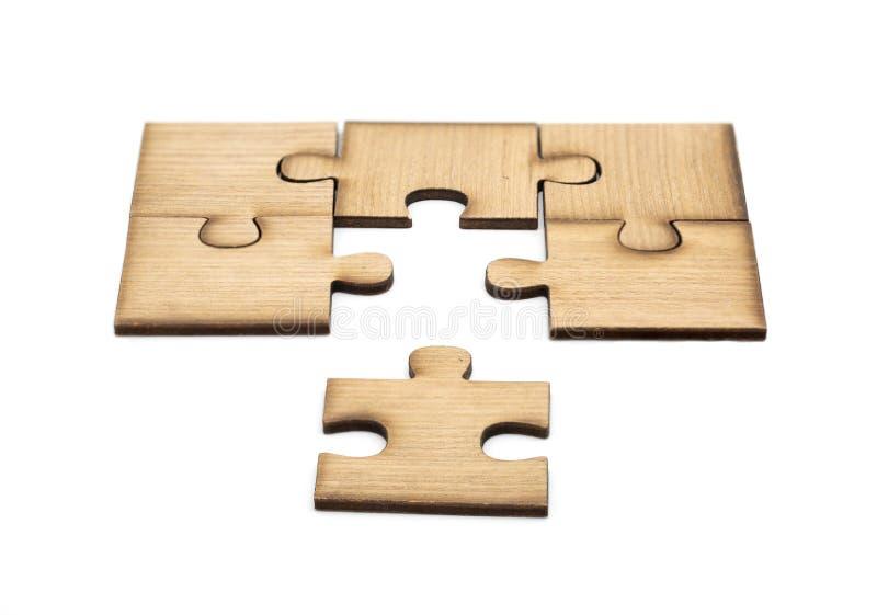 Collocazione mancando un pezzo di puzzle il concetto di affari, pezzi di puzzle di legno ? collegato isolato insieme su fondo bia fotografie stock