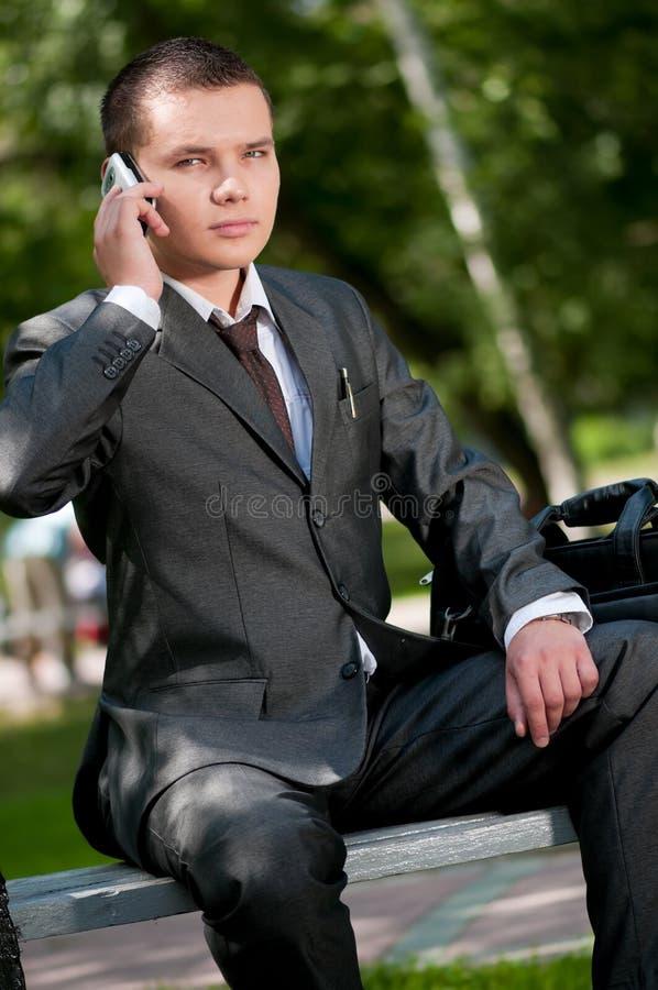 Colloquio dell'uomo di affari dal telefono mobile. Allievo fotografia stock libera da diritti