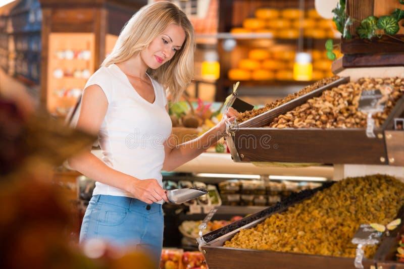 Colmado - compras sonrientes de la mujer en supermercado fotos de archivo libres de regalías