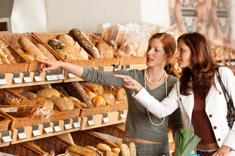 Colmado: Dos mujeres jovenes que eligen el pan imágenes de archivo libres de regalías