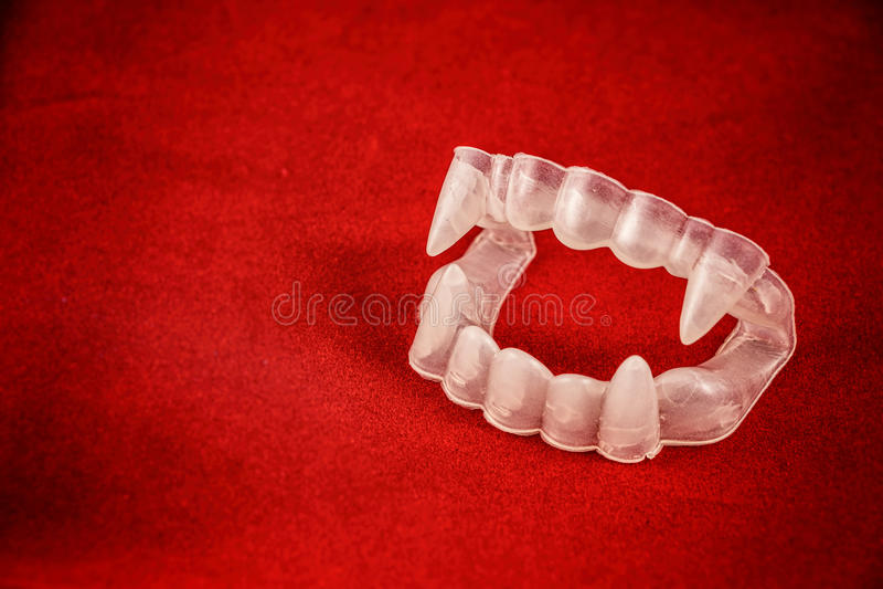 Colmilhos do traje do vampiro no vermelho fotos de stock royalty free