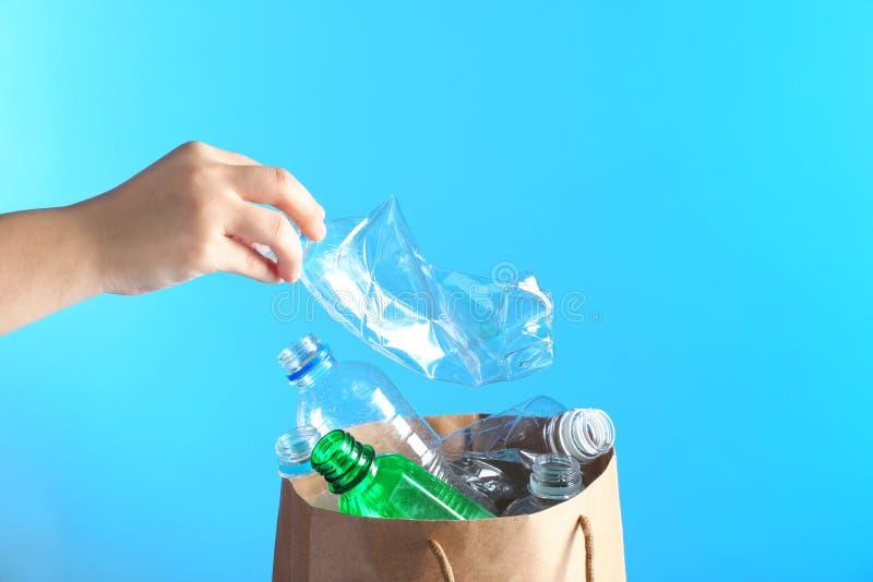 A colocação da mulher usou a garrafa plástica no saco de papel no fundo da cor, close up com espaço para o texto fotos de stock