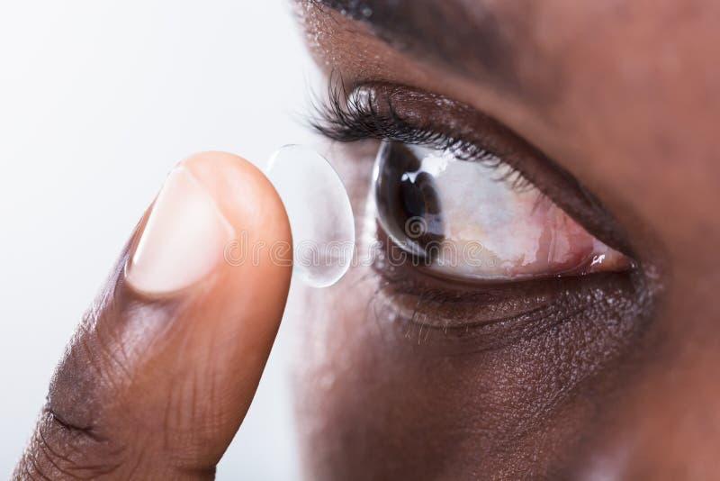 A colocação da pessoa contacta a lente no olho imagens de stock