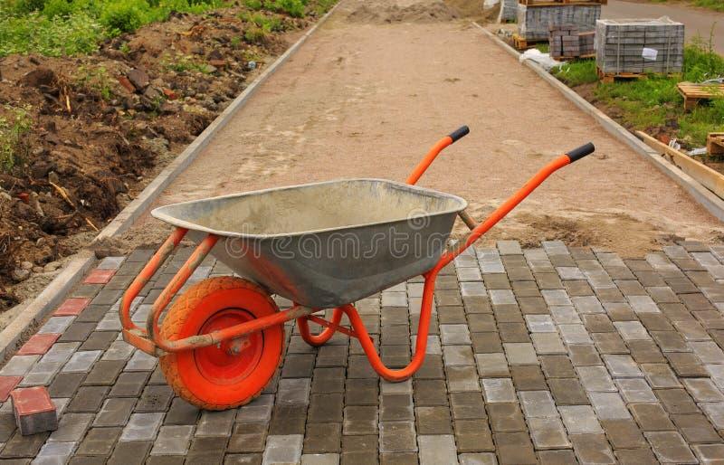 Colocação de pavimentos Reparando o passeio wheelbarrow fotos de stock royalty free