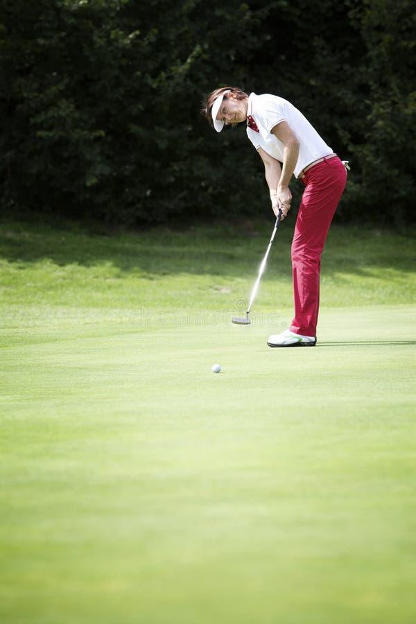 Colocação fêmea do jogador de golfe foto de stock