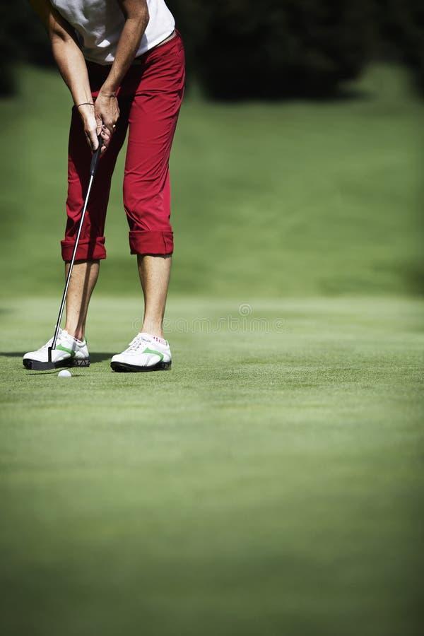 Colocação fêmea do jogador de golfe fotografia de stock royalty free