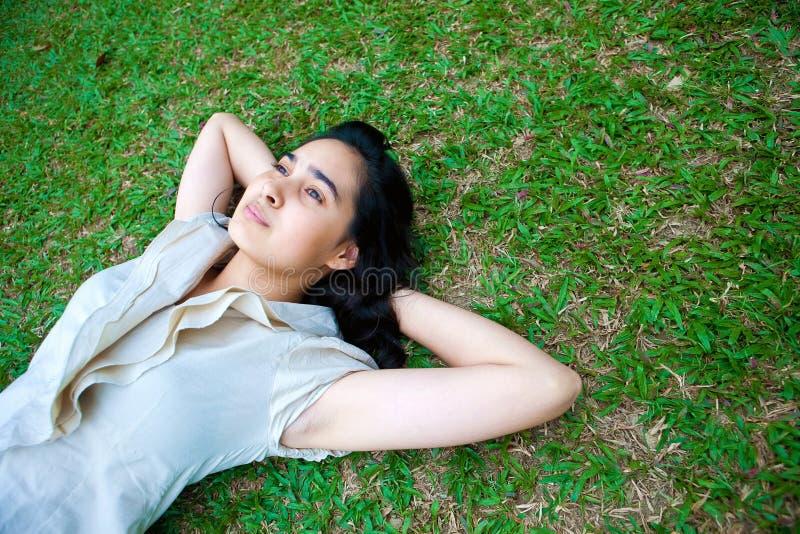 Colocação fêmea nova na grama, pensando imagens de stock royalty free