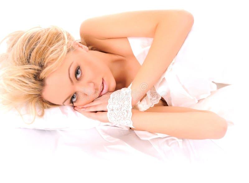 Colocação na mulher da cama imagens de stock royalty free