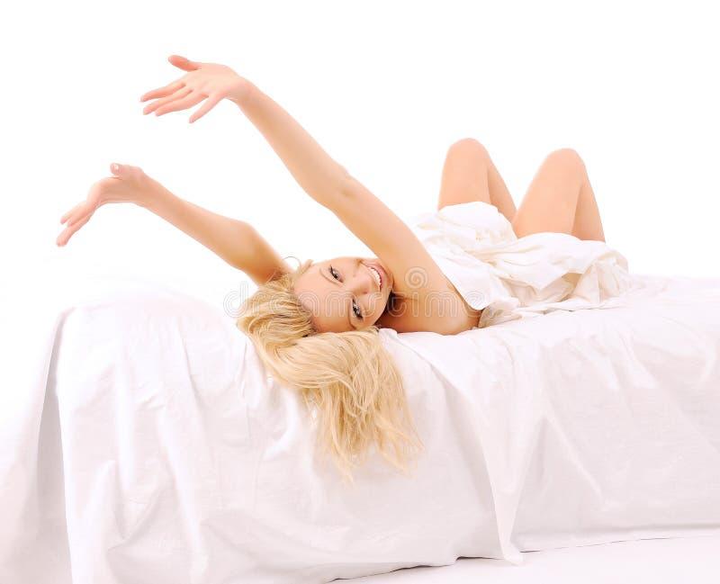 Colocação na mulher encantadora da cama foto de stock royalty free