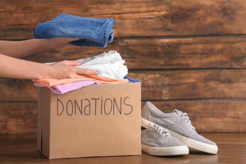 A colocação voluntária da fêmea veste-se na caixa da doação fotografia de stock