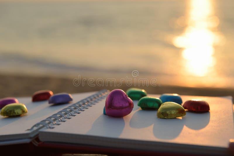 Colocación colorida de la forma del corazón del chocolate en el libro imagenes de archivo