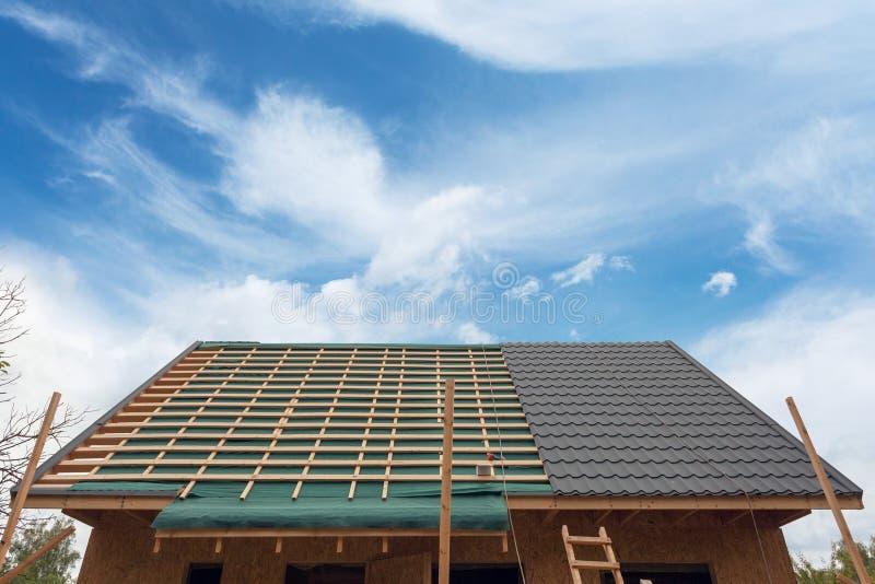 Colocación de la teja del metal en el tejado Casa bajo construcción con hierro del destornillador y de la techumbre fotografía de archivo libre de regalías