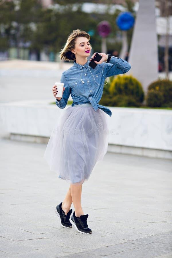 Colocación de puntillas de la muchacha de baile en la calle, la camisa de los tejanos que lleva y la falda gris hermosa de Tulle  foto de archivo libre de regalías