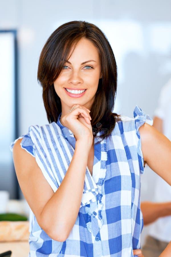 Colocación sonriente de la mujer joven con la toalla de cocina foto de archivo