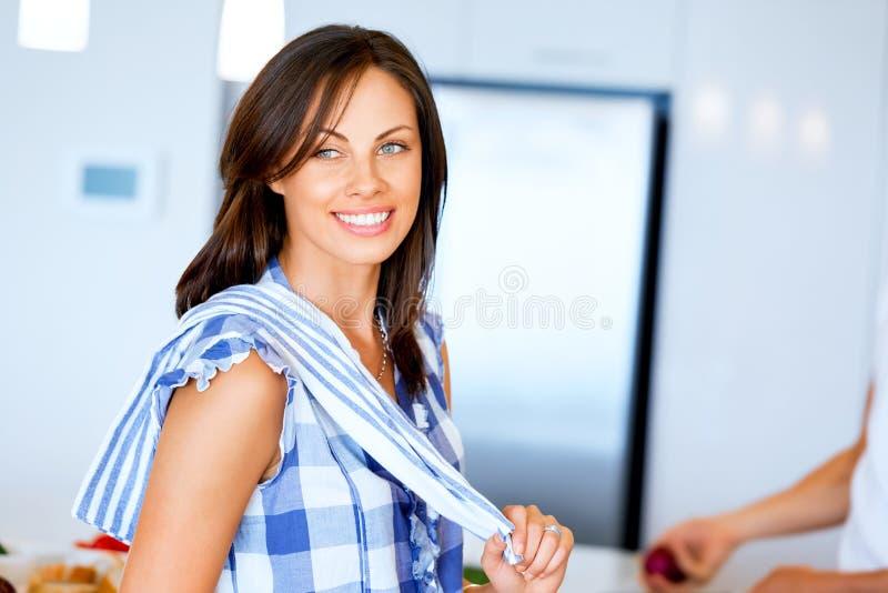 Colocación sonriente de la mujer joven con la toalla de cocina imagenes de archivo