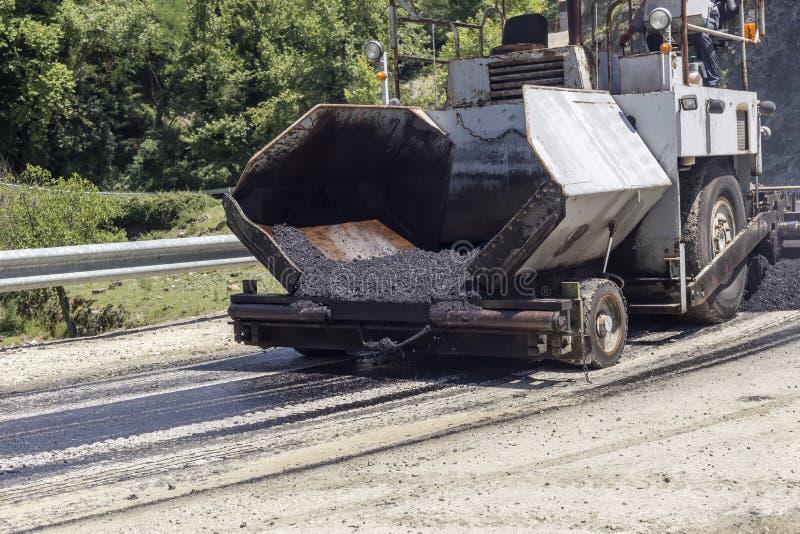 Colocando o asfalto nas montanhas em uma estrada estreita imagem de stock