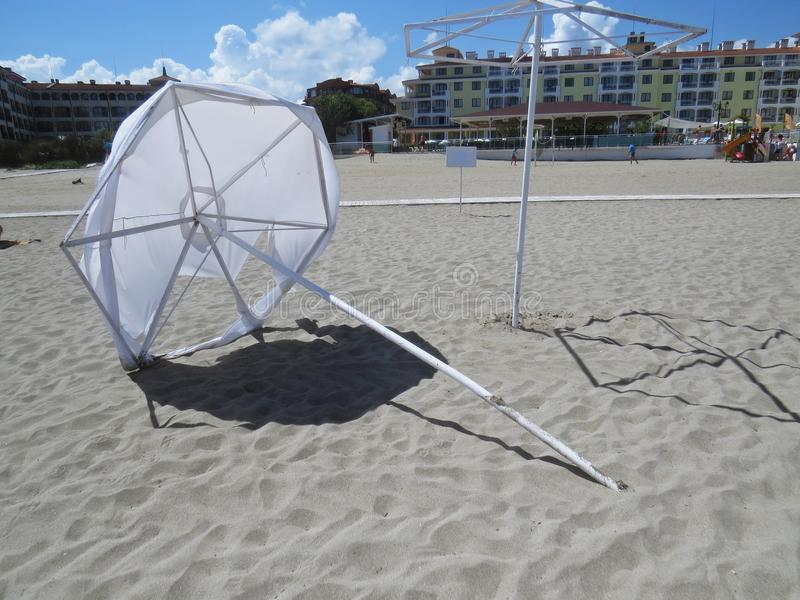 Colocando o guarda-chuva branco destruído do parasol da praia da areia no vento que protege de Sun durante férias exóticas, Tsare fotos de stock royalty free
