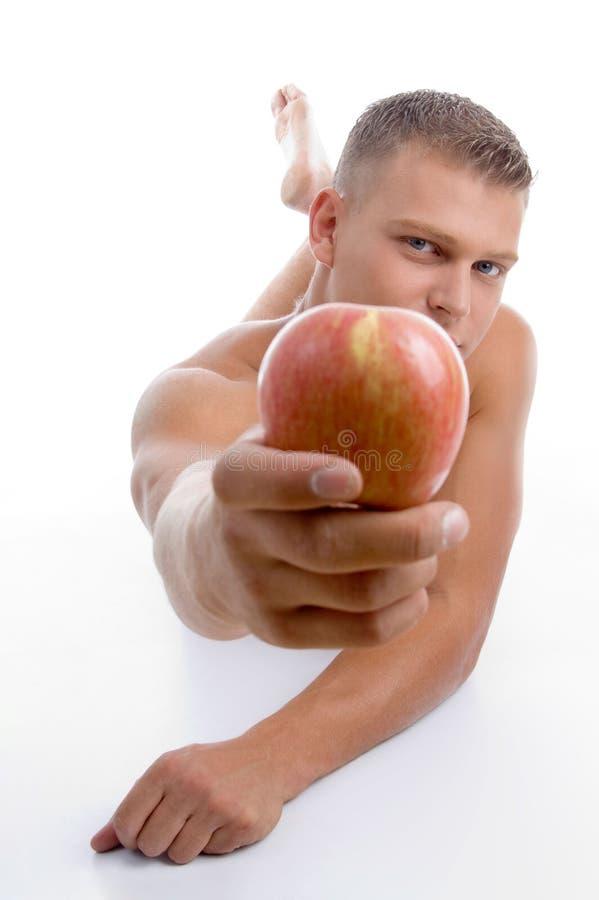 Colocando o indivíduo apto que mostra a maçã imagem de stock