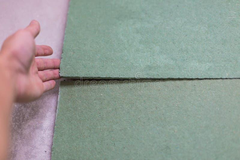 Colocando o revestimento estratificado Forro isolado no assoalho pronto para a estratificação de madeira do efeito do fechamento  imagem de stock royalty free