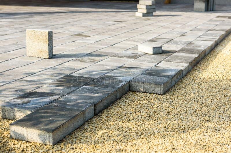 Colocando pavimentos concretos cinzentos no pa da entrada de automóveis do pátio da casa imagem de stock royalty free