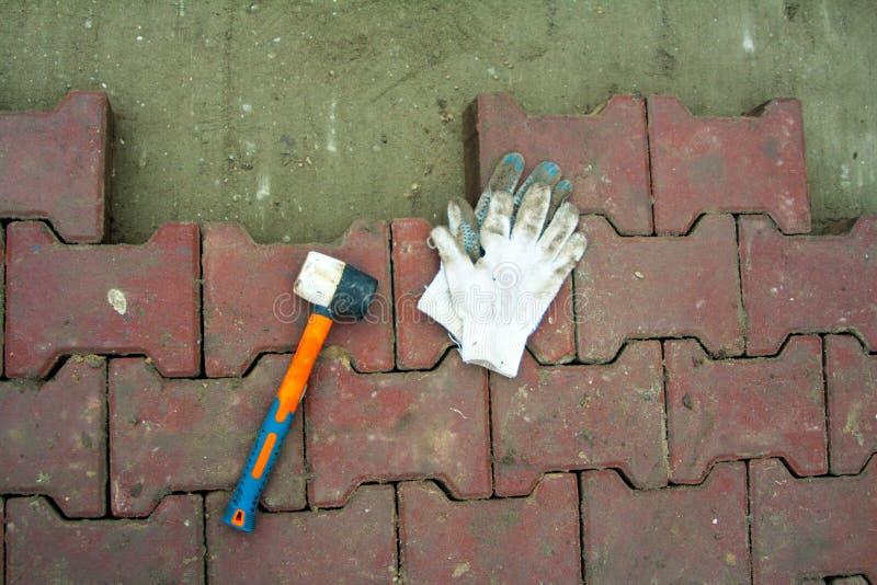 Colocando pavimentos pelo close-up do mosaico Estrada que pavimenta, construção Trabalhadores que colocam o pavimento da pedra Co imagem de stock royalty free